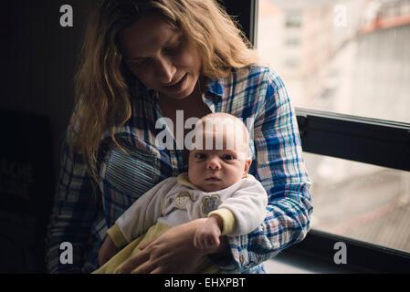 Portrait d'une mère avec son nouveau-né assis près d'une fenêtre Banque D'Images
