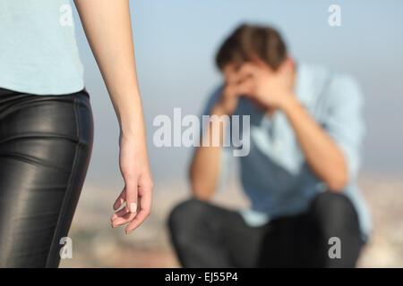 Rupture d'un couple avec un homme triste dans l'arrière-plan et l'petite amie lui laissant au premier plan Banque D'Images