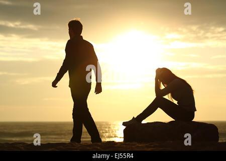 Silhouette Couple briser un rapport sur la plage au coucher du soleil Banque D'Images