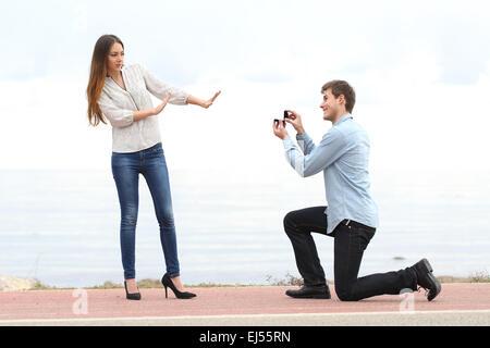 Rejet de la proposition lorsqu'un homme heureux demande en mariage à une femme sur la plage Banque D'Images