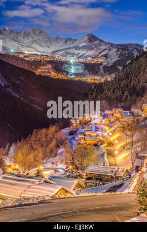 Petit village sur la montagne enneigée, hiver, heure bleue, tout en légèreté, piste de ski, montagne dans la distance Banque D'Images