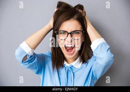 Angry businesswoman touching her hair et criant sur fond gris. En chemise bleue et portant des lunettes. Looking Banque D'Images