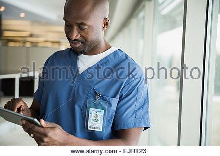 Chirurgien using digital tablet at window Banque D'Images