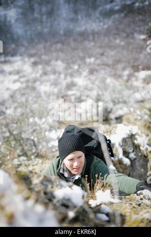 Un homme de la randonnée dans les montagnes de grimper une steep rock face. Banque D'Images