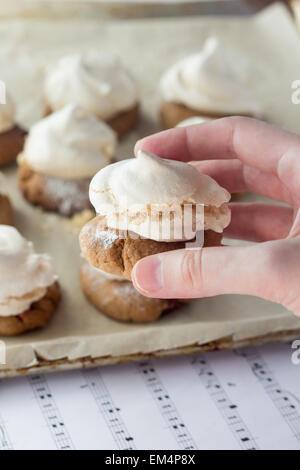 Coup de doigts biscuits sablés avec de la meringue holding Banque D'Images