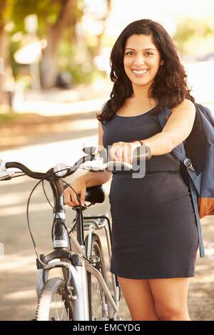 Jeune femme en vélo le long de la rue Banque D'Images
