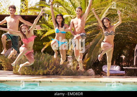 Groupe d'amis adolescents Jumping Into Swimming Pool Banque D'Images