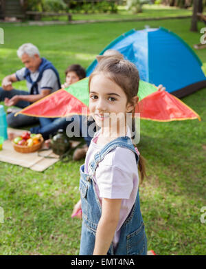Smiling Girl standing at campsite Banque D'Images