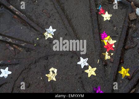 Étoiles colorés dans de l'eau sale sur le dessus du couvercle de trou d'un dark metal Banque D'Images