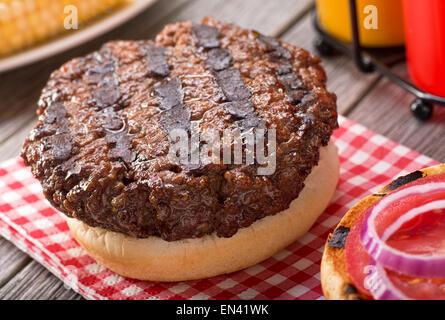 Un barbecue avec grill hamburger juteux de marques sur une table de pique-nique rustique à la tomate, oignon, moutarde, Banque D'Images