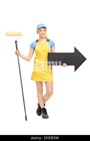 Portrait d'une femme peintre dans un uniforme jaune tenant un rouleau à peindre et une grande flèche noire pointant Banque D'Images
