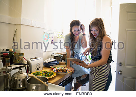La cuisine d'amis using digital tablet in kitchen Banque D'Images