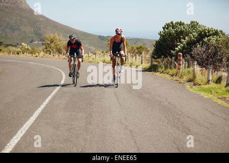 Faire du vélo cycliste sur route ouverte. Les triathlètes du vélo sur des bicyclettes. La pratique de triathlon. Banque D'Images