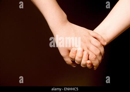 L'amitié pour toujours. Les enfants se tenant la main, Close up, copiez l'espace. Banque D'Images