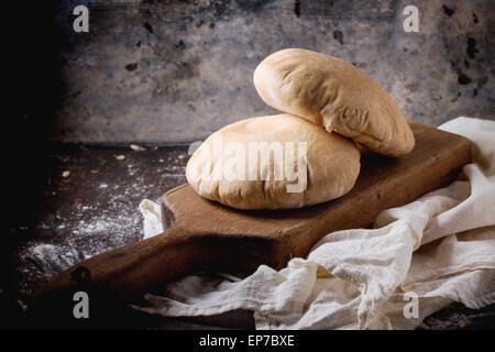 Deux de farine de pain de pita sur planche à découper en bois, servi avec de la farine sur la table sombre Banque D'Images