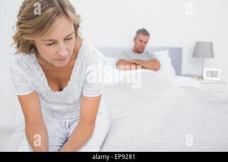Couple assis sur les extrémités opposées du lit après une lutte Banque D'Images