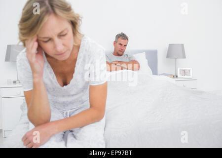 Couple malheureux aux extrémités opposées du lit après une lutte Banque D'Images