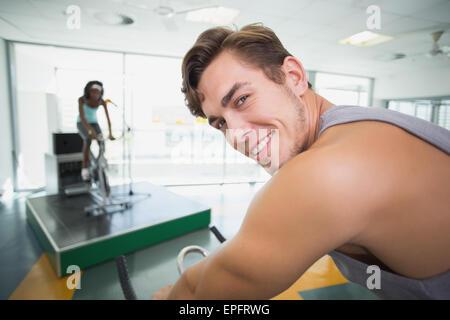 Handsome man smiling at camera en classe spin Banque D'Images