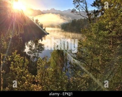 Vue sur les Alpes du sud du lac Matheson dans la brume matinale. L'île du Sud, Nouvelle-Zélande. Banque D'Images