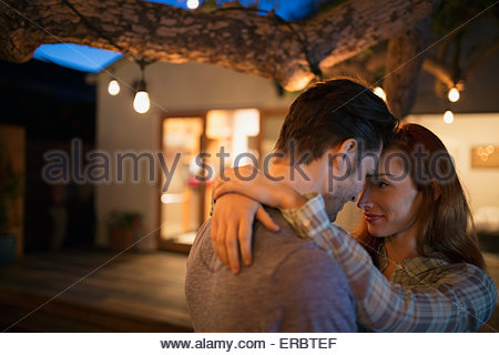 Affectionate couple hugging under tree with string lights Banque D'Images