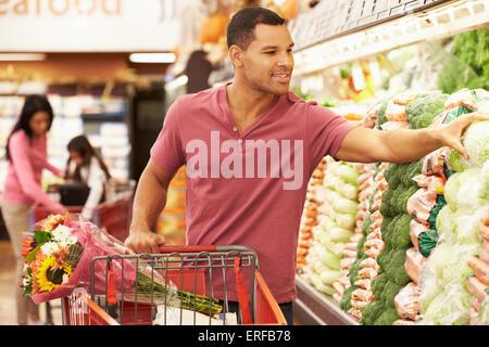 Man Pushing Trolley par produire compteur dans un supermarché Banque D'Images