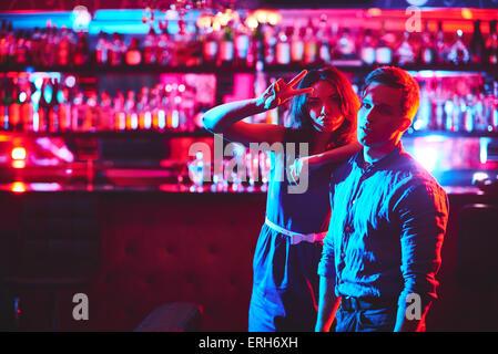 Jeune couple looking at camera en bar de nuit club Banque D'Images