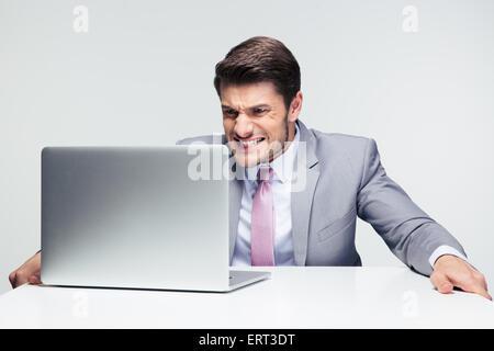 Homme d'affaires inquiets assis à la table avec un ordinateur portable sur fond gris Banque D'Images
