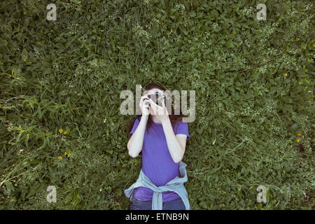 Woman lying in grass photographier sky Banque D'Images