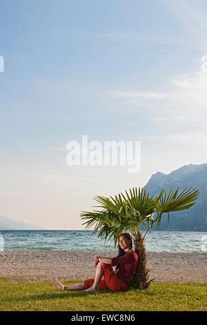 Woamn assis sous un palmier miniature au Lac de Garde en Italie du nord Banque D'Images