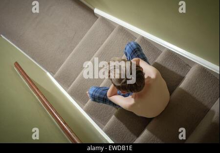 Un enfant assis sur les escaliers avec sa tête dans ses mains à la colère Banque D'Images