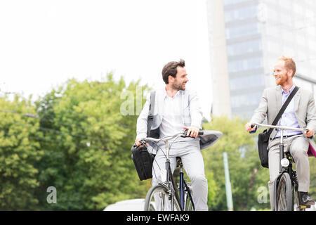 Hommes d'parler tout en la bicyclette en plein air Banque D'Images