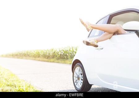 La section basse de woman in car on country road contre ciel clair Banque D'Images