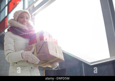 Smiling woman in vêtements chauds transportant des cadeaux empilés par fenêtre Banque D'Images