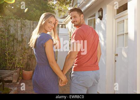 Piscine shot of young caucasian couple walking à leur maison se tenant la main, à la fois regard sur les épaules Banque D'Images