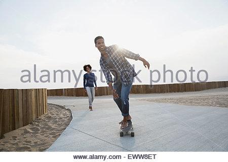Planche à roulettes sur le chemin de la plage Man Banque D'Images