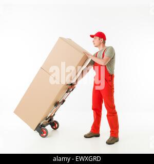 Delivery man holding push cart chargé avec des boîtes en carton, sur fond blanc Banque D'Images