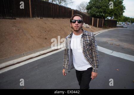 Jeune homme hipster looking at camera en marchant sur la route de banlieue Banque D'Images