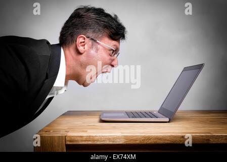 L'homme assis à la table et de crier sur son ordinateur portable Banque D'Images