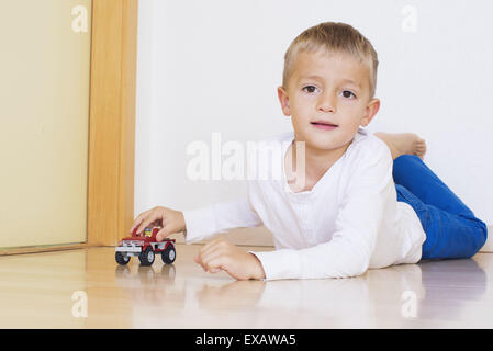 Boy lying on floor Playing with toy truck Banque D'Images