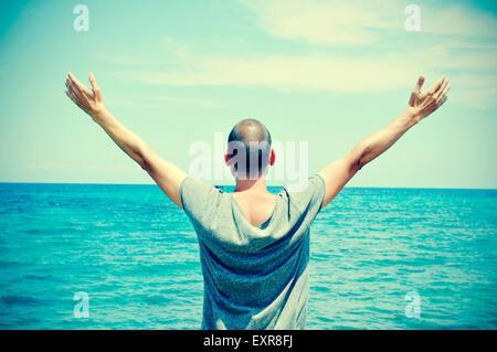 Libre d'un jeune homme de race blanche vu de derrière avec les bras en l'air en face de l'océan, se sentir libre, Banque D'Images