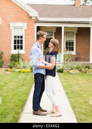 Jeune couple debout sur sentier en face de la maison Banque D'Images