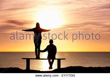 Silhouette de couple, debout sur un banc de travail avec les bras tendus, contre le coucher du soleil sur l'océan Banque D'Images