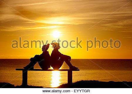 Silhouette de couple, assis dos à dos sur un banc, contre le coucher du soleil sur l'océan Banque D'Images