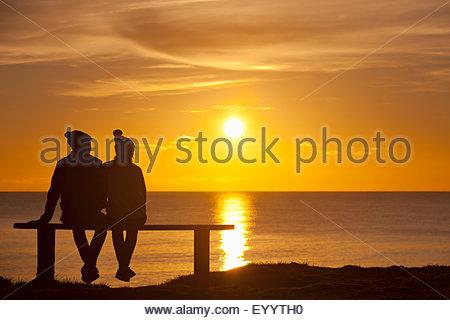 Silhouette de couple, assis sur un banc, contre le coucher du soleil sur l'océan Banque D'Images