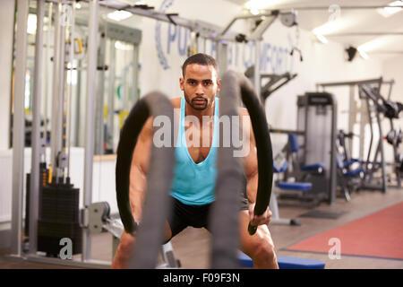 Jeune homme travaillant sur des cordes de combat dans une salle de sport Banque D'Images