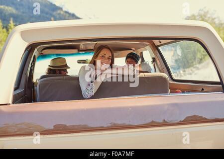 Young woman leaning against backseat regardant par la fenêtre d'un pick-up Banque D'Images