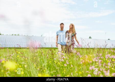 Jeune couple en train de marcher à travers champ en regard de la ferme solaire Banque D'Images