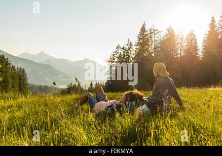 Autriche, Tyrol, Tannheimer Tal, jeune couple reposant sur pré alpin Banque D'Images