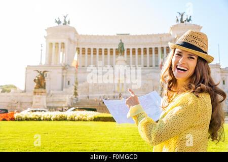 De cette façon! Une femme riant touristes détenteurs d'une carte est souriant et pointant vers le monument de la Banque D'Images