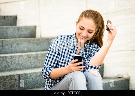 Adolescent - jeune femme de manger du chocolat en rue et à la recherche dans le téléphone Banque D'Images